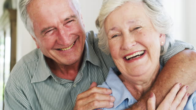 4k video footage of a happy senior couple in a loving embrace at home